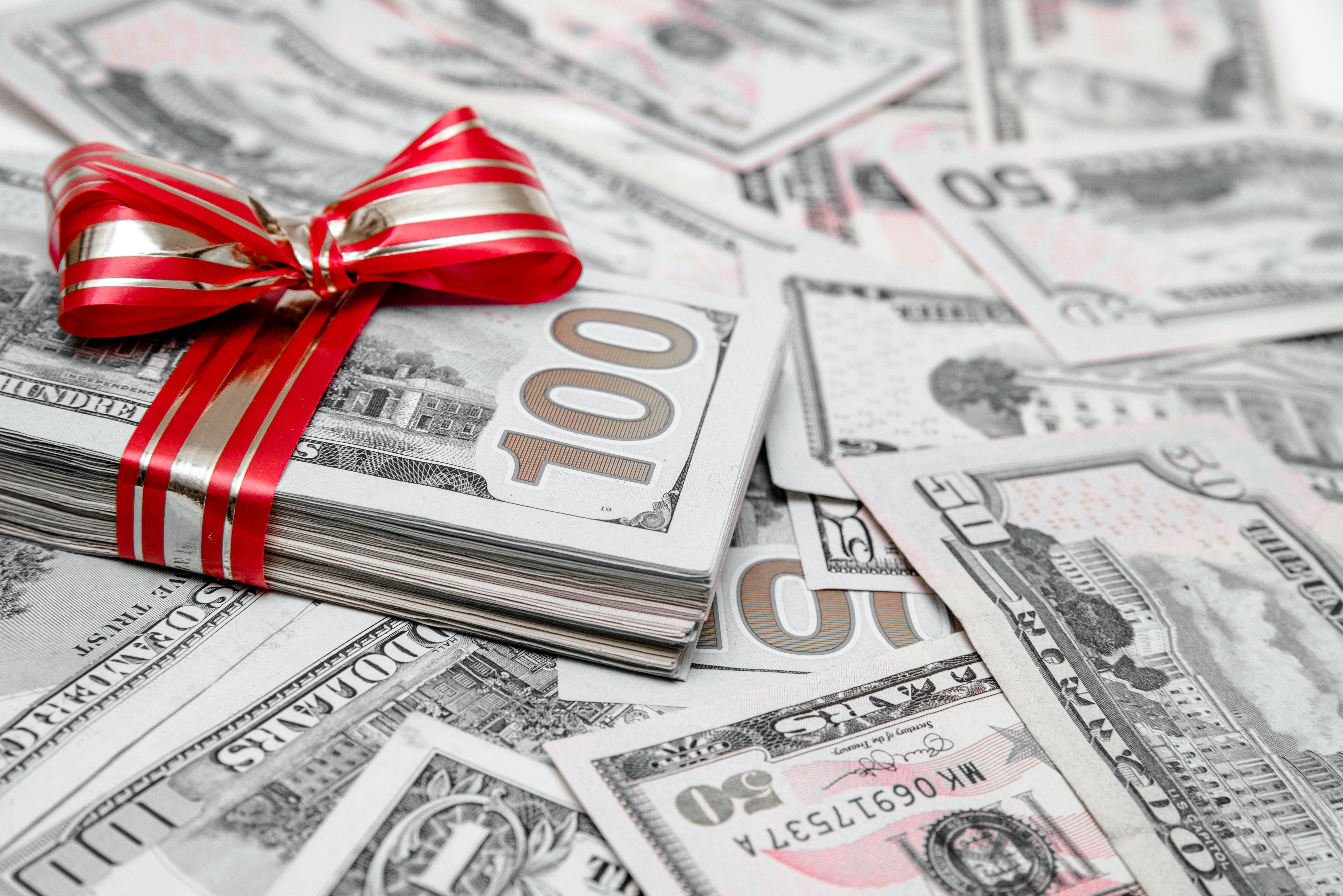 Stack of cash wrapped in a red bow