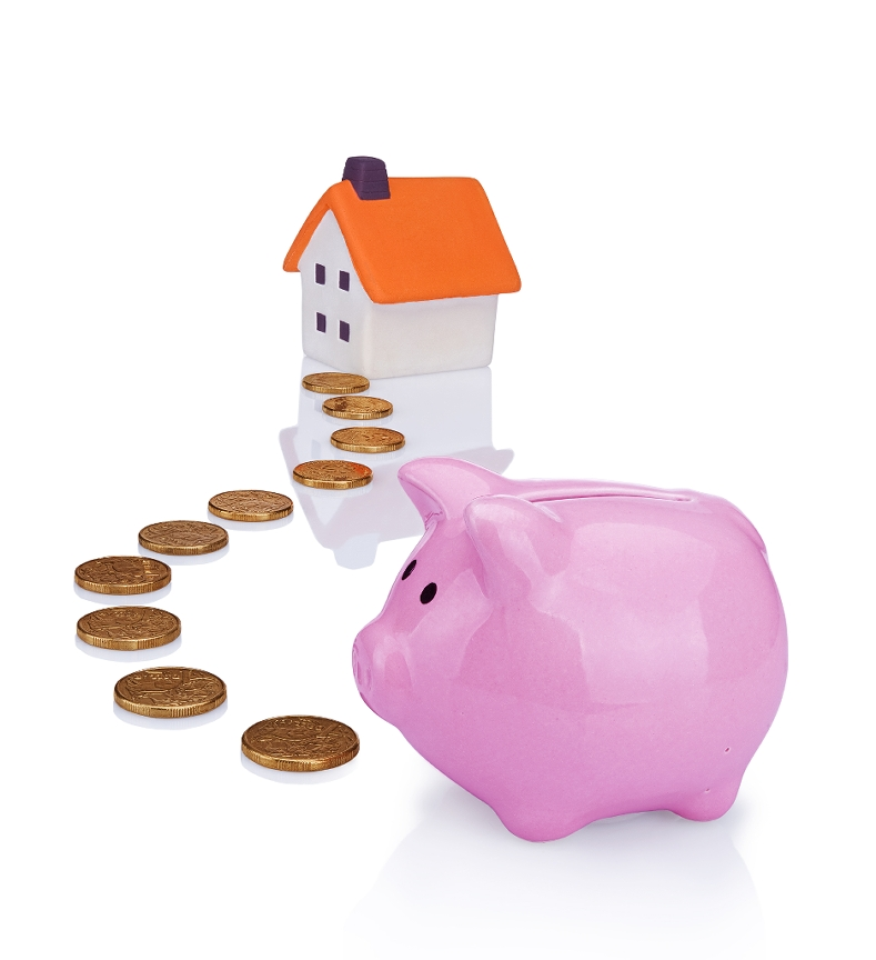A pink piggy bank with coins leading up to a miniature house