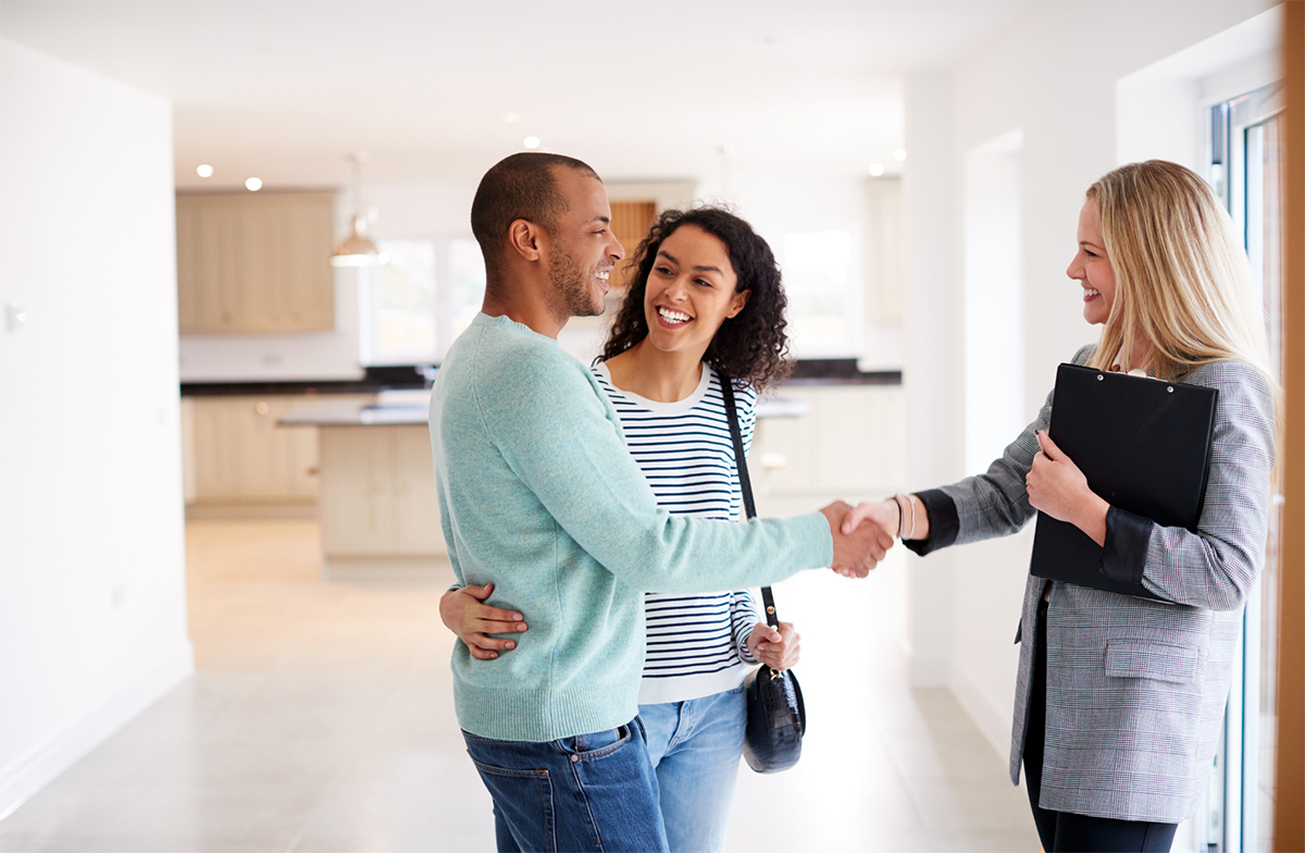 Young couple shaking hands with real estate agent