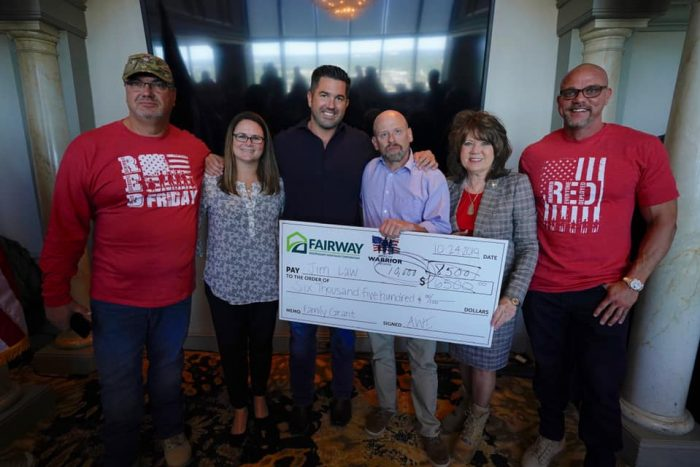 Fairway employees at an AWI event with large check