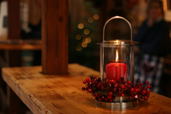 Lit red holiday candle on a wood table