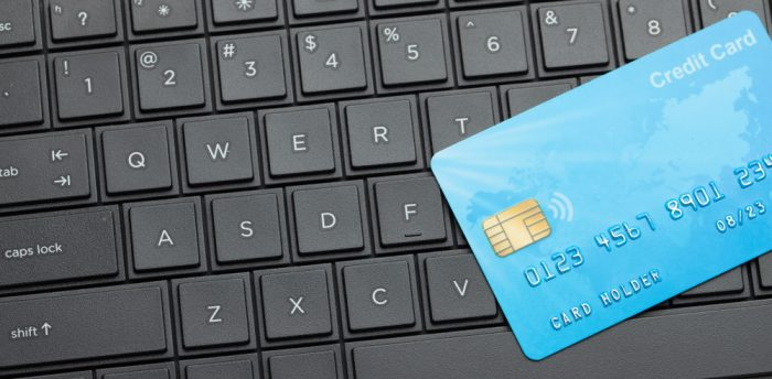 A blue credit card laying on a keyboard