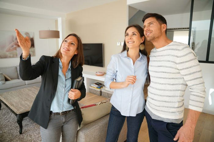A real estate agent showing a couple a home