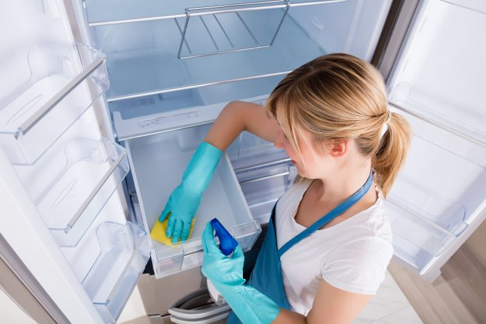 a woman cleaning her refrigerator