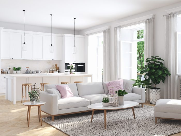 a fully furnished, mostly white living room and kitchen